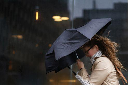 A woman struggles with her umbrella in the wind during a heavy rain storm in New York
